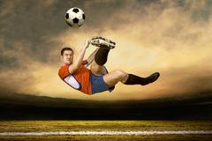 Stock Photo of Football player with ball in action under rain outdoors