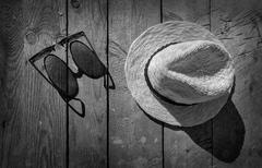 Sunglasses and hat on the wooden texture in sunday. Stock Photos