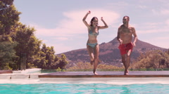 Happy couple jumping in the swimming pool Stock Footage