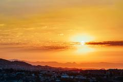 Beautiful Sunset Sunrise Over Mountain and city - stock photo