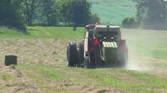 Farmers cutting and harvesting hay before it rains on family farm - stock footage