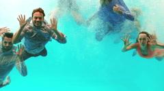 Happy friends swimming underwater Stock Footage