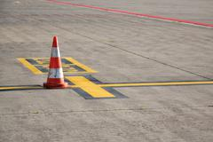 Orange traffic cone stand on airport runway in sunny day - stock photo