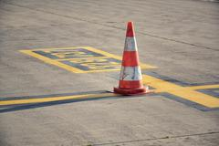 Orange traffic cone stand on airport runway in sunny day Stock Photos