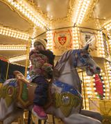 Adorable little girl on a carousel at Christmas market - stock photo