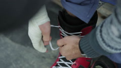 Snowboarder tying shoelaces. Close-up Stock Footage