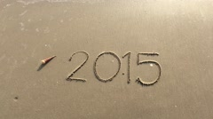 Goodbye 2015 - writing in sand washed away by waves Stock Footage