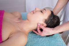 Natural mature woman having a massage at her auricle Stock Photos