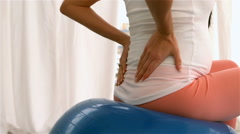 Pregnant woman touching back sitting on fitness ball Stock Footage