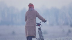 Young woman riding a bicycle across the field. Stock Footage