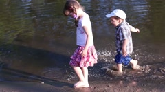 Little boy runs on water on edge of pond near girl walking on edge of pond Stock Footage