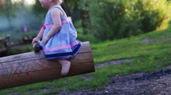 Little cute girl with blond hair in dress rides on wooden swing Stock Footage