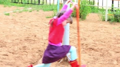 Little cute girl spinning quickly on playground at summer day Stock Footage