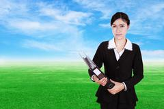 business woman holding folder documents with green grass field - stock photo