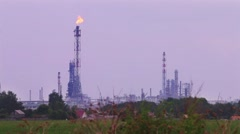 Tall gas flare of refinery plant near green field on cloudy day Stock Footage