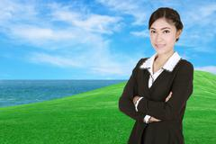 Business woman , crossed arms, with green grass field and sea Kuvituskuvat