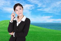 Business woman thinking with green grass field and sea - stock photo