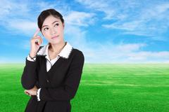 Business woman thinking with green grass field and blue sky - stock photo