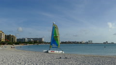 Palm beach with a catamaran and hotels at the background on Aruba Stock Footage