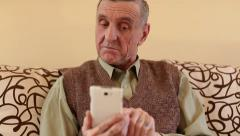 Senior man looks and flips through the photos in her smartphone Stock Footage