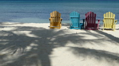 Colorful chairs at palm beach Aruba with palm tree reflection at the beach Stock Footage