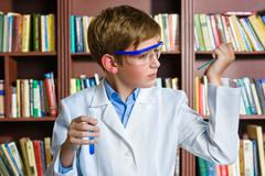 Cute boy doing biochemistry research in chemistry class - stock photo