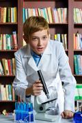 Cute boy doing biochemistry research in chemistry class - stock photo