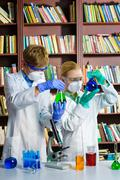 Cute boy and girl doing biochemistry research in chemistry class - stock photo