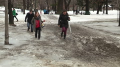 Students walk to campus in snow slush and deep water puddles Stock Footage