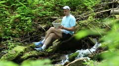 Man with tablet computer sits near small river in forest Stock Footage