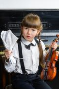 distraught or distressed girl clutching her head and holding a violin - stock photo