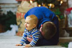 Father plays with the child In Home Holiday Living Room. House Decorating By Stock Photos