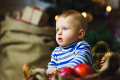 One years old child celebrating holidays near Christmas tree Stock Photos