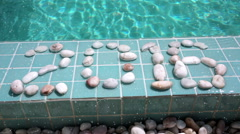 "The inscription "" 2016 "" is laid out by pebble on  pool side - stock footage"