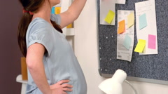 Pregnant woman sticking note on board Stock Footage