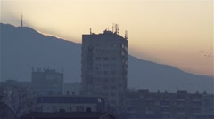 Sunset over the mountains and the city of apartment blocks in slow motion Stock Footage