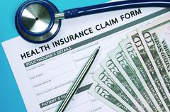Health insurance claim form with money and stethoscope for insurance concept - stock photo