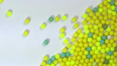 Rolling yellow small balls on white background - screen filled - slow motion Stock Footage