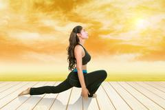 Stock Photo of woman doing yoga exercise on wood floor with field at sunset