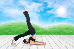 woman doing yoga exercise on wood floor with green grass and sky - stock photo