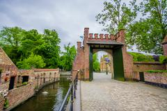 Stock Photo of BRUGES, BELGIUM - 11 AUGUST, 2015: Small waterchannel sorrounded by brick walls