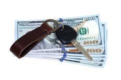 Car key on money isolated on white background - stock photo