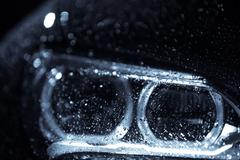 Car headlight with rain drops Stock Photos