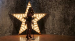 expression woman singer with microphone, dances. shining star in the background - stock footage