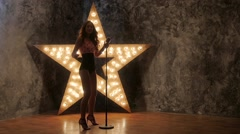 Beautiful Singing Girl. Beauty Woman with Microphone, shining star in the Stock Footage