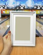 Wooden frame in woman hands on the background of bowling lanes - stock photo
