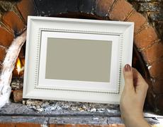 Wooden frame in woman hands. Warm Hearth on the background - stock photo