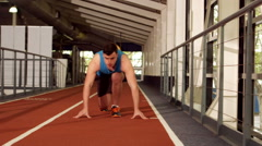 Stock Video Footage of Young man ready to race on running track