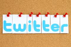 Twitter logotype printed on paper, cut and pinned on cork bulletin board. Stock Photos