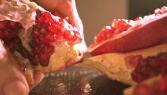 Man breaking a half of pomegranate - stock footage